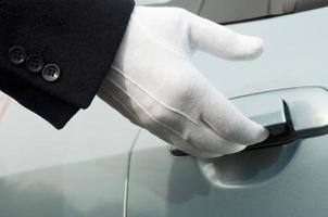 porta della macchina con apertura a mano in uniforme bianca con guanti formali foto