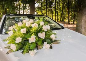 bouquet di rose sulla macchina della sposa foto