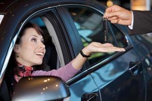 giovane donna che riceve le chiavi della macchina dal venditore di auto