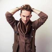 attraente giovane uomo in un maglione marrone posa in studio.