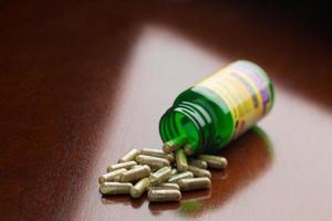 integratori a base di erbe che fuoriescono da una bottiglia di medicina aperta foto