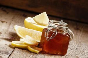 miele con limone, erboristeria e concetto di cibo sano foto