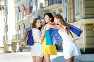 abbracciare le amiche. tre ragazze attraenti che tengono i sacchetti