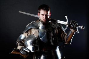cavaliere in armatura da combattimento con una spada sulle spalle foto