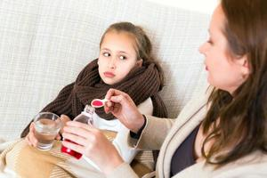 madre che dà syrop per la tosse alla figlia foto