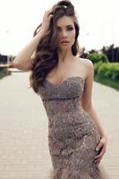 donna sensuale con capelli scuri in un lussuoso abito di paillettes foto