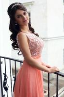 bella donna in abito di lusso in posa sul balcone foto