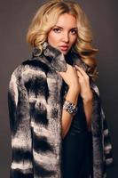 donna sensuale con capelli ricci biondi che indossa cappotto di pelliccia di lusso foto