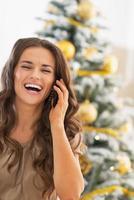 felice giovane donna parlando cellulare vicino all'albero di Natale