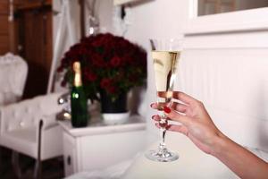 mano della donna che tiene un bicchiere di champagne in camera da letto di lusso foto