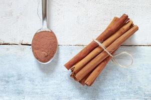 bastoncini di cannella legati accanto a un cucchiaio con cannella in polvere