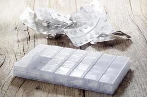 distributore di pillole pieno su legno rustico foto