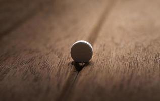 pillola pericolosa ancora vita su fondo di legno scuro foto