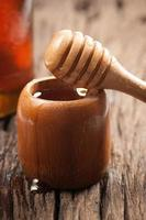 miele naturale fresco in un barattolo con un cucchiaio di miele foto