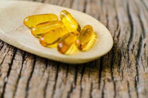olio di pesce sul cucchiaio di legno foto