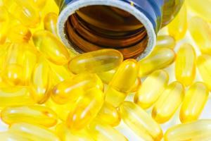 pillole di olio di pesce fuoriuscite dal contenitore foto