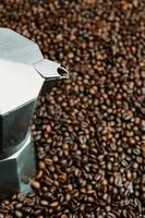 pentola in acciaio circondata da chicchi di caffè foto