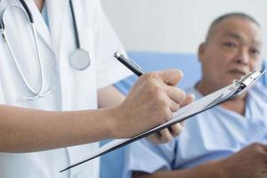 medico scrivendo prescrizione per il paziente foto