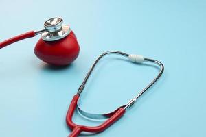 stetoscopio e cuore rosso su sfondo blu foto