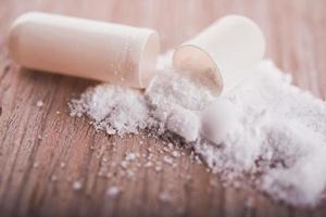 pillola capsula bianca aperta con farmaco in polvere foto