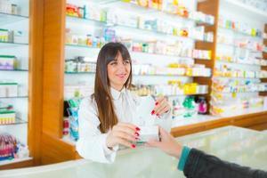 donna farmacista in farmacia parlando e aiutando il cliente foto