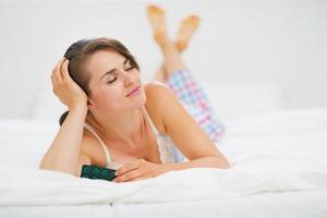 donna felice posa a letto con blister di pillole foto