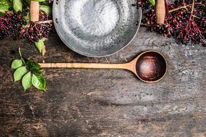 mazzo di bacche di sambuco con pentola vuota e cucchiaio per cucinare