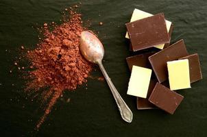 barrette di cioccolato con un mucchio di polvere di cacao foto