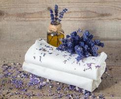 olio di lavanda, fiori di lavanda e asciugamani bianchi da bagno. foto