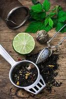 infuso di tè con lime e menta su fondo in legno foto