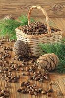 noci di cedro nel cesto di vimini su un tavolo di legno foto