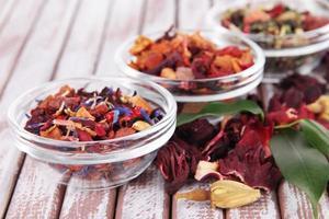 tè secco aromatico in ciotole su fondo in legno foto
