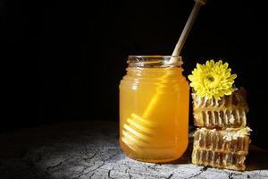 vasetto di miele e favi su uno sfondo di legno foto