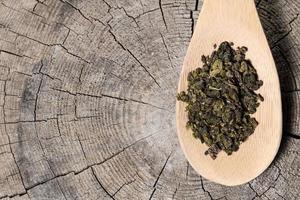 cucchiaio con tè oolong su fondo in legno foto