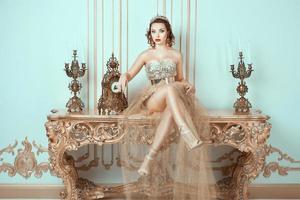 ragazza con corona la testa seduta su un vecchio tavolo. foto