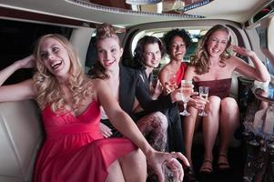 gruppo di ragazze con bevande si siedono in una limousine foto