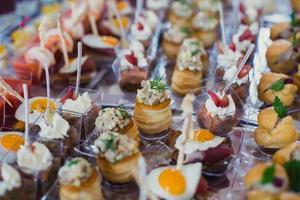 tavolo per banchetti catering splendidamente decorato con diversi stuzzichini antipasti foto