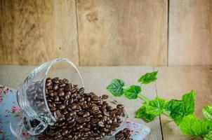 chicchi di caffè con la tazza sulla tavola di legno foto