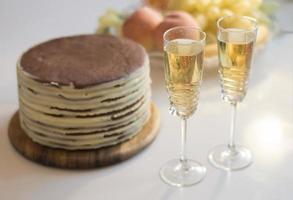 vacanza con due bicchieri di champagne, torta e frutta foto