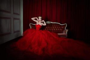 bella ragazza in abito lungo rosso e corona reale foto
