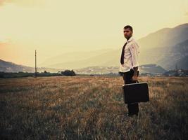 uomo sanguinante che cammina con la valigetta foto