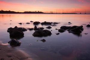 tramonto su barche con rocce in primo piano foto