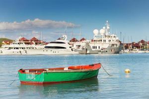 barca da pesca con sfondo di yacht di lusso, eden island, mahe