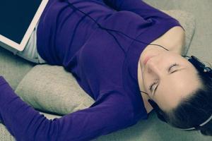 giovane donna che utilizza le cuffie tavoletta digitale a casa foto