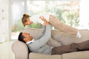 padre sdraiato sul divano e sollevando sua figlia foto