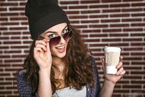 concetto di giovane donna alla moda vicino al muro di mattoni