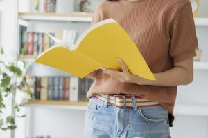 primo piano della donna che legge un libro giallo