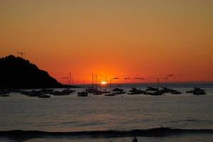 barche a vela in mare durante il tramonto foto