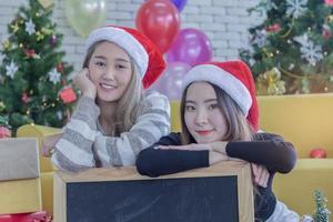 due donne in posa indossando cappelli di Babbo Natale