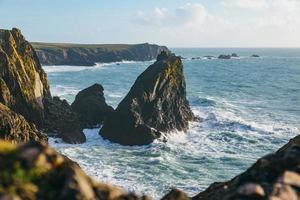 paesaggio marino roccioso durante il giorno foto
